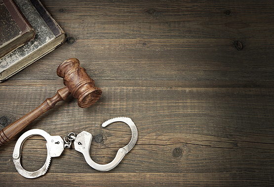 handcuffs and a gavel on a wooden table