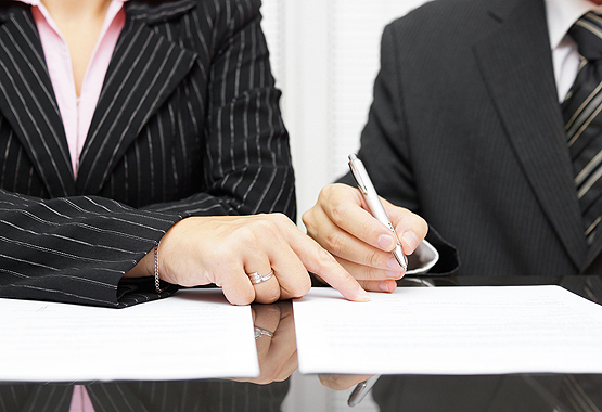 two lawyers signing a contract