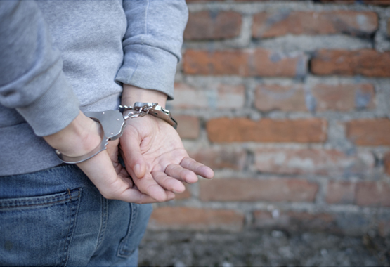 man in gray sweater with handcuffed hands behind his back