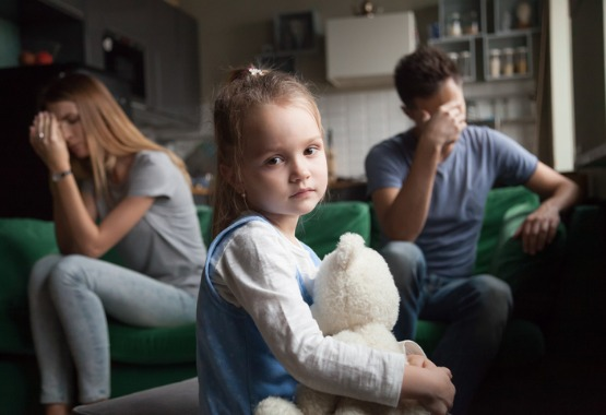 A small girl between two fighting parents in the background, needing a child custody attorney in Pekin IL