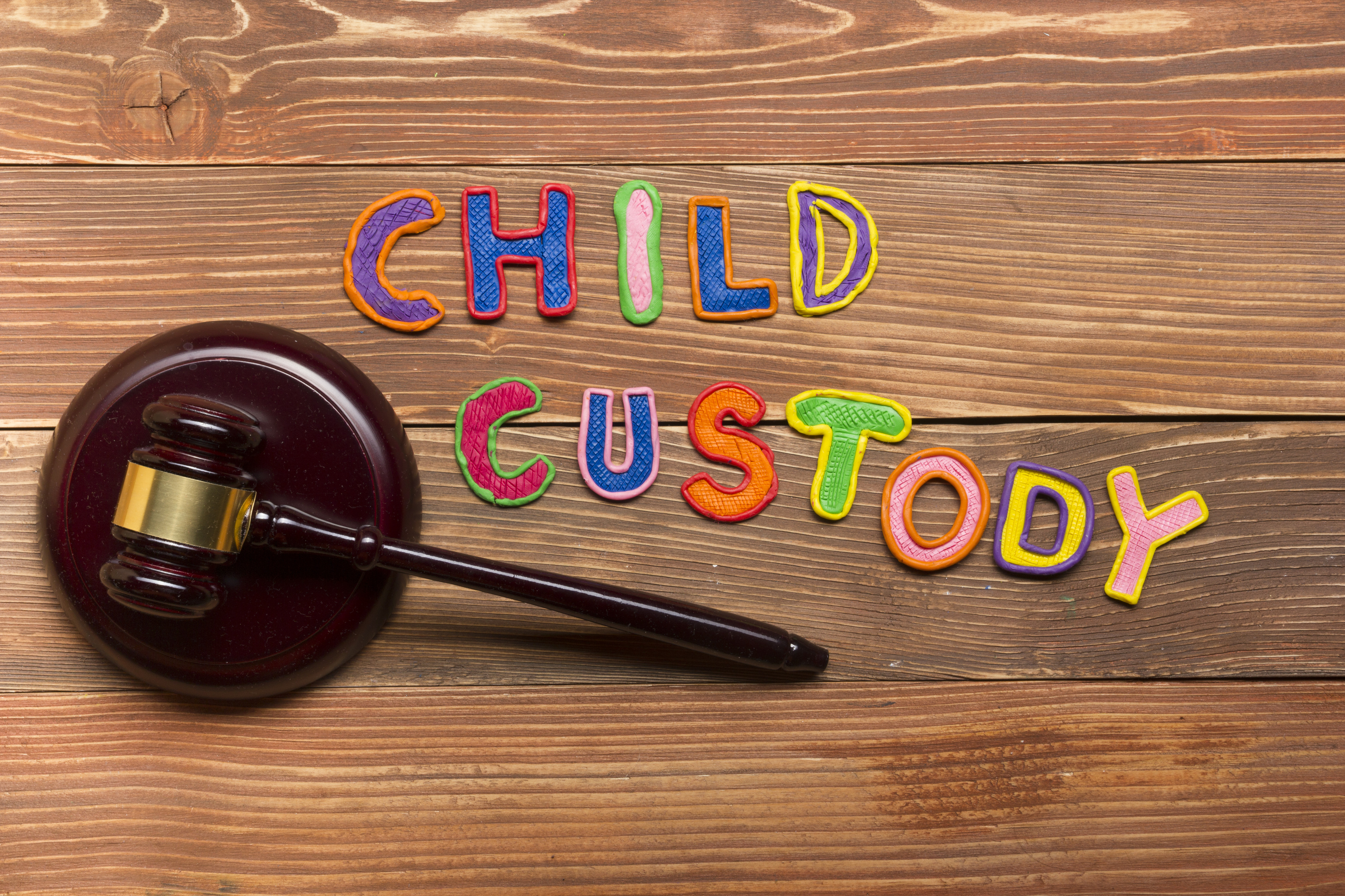 """A gavel with the colorful words """"child custody"""" spelled out next to it"""