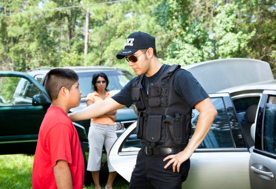 A police officer talking to a child after getting caught in a bad situation