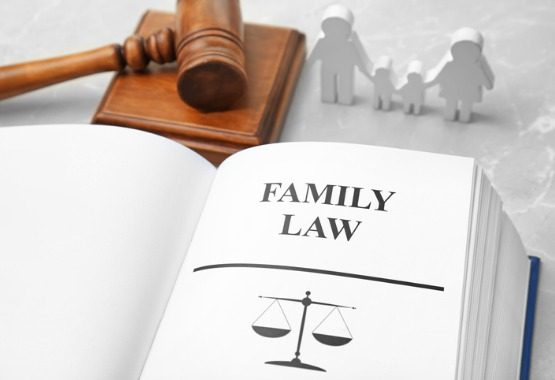 A law book, gavel and wood figures of a family, representing a family law attorney in Pekin IL