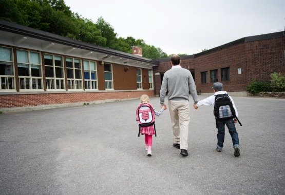 A father taking his two children to school in East Peoria IL