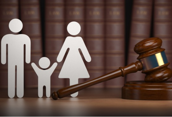 A cutout of a man and a woman with a child in between them next to a gavel, representing Divorce Lawyers in East Peoria IL