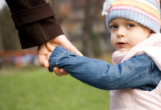 Young girl holding hands with her parent after meeting with Child Custody Lawyers in Pekin IL